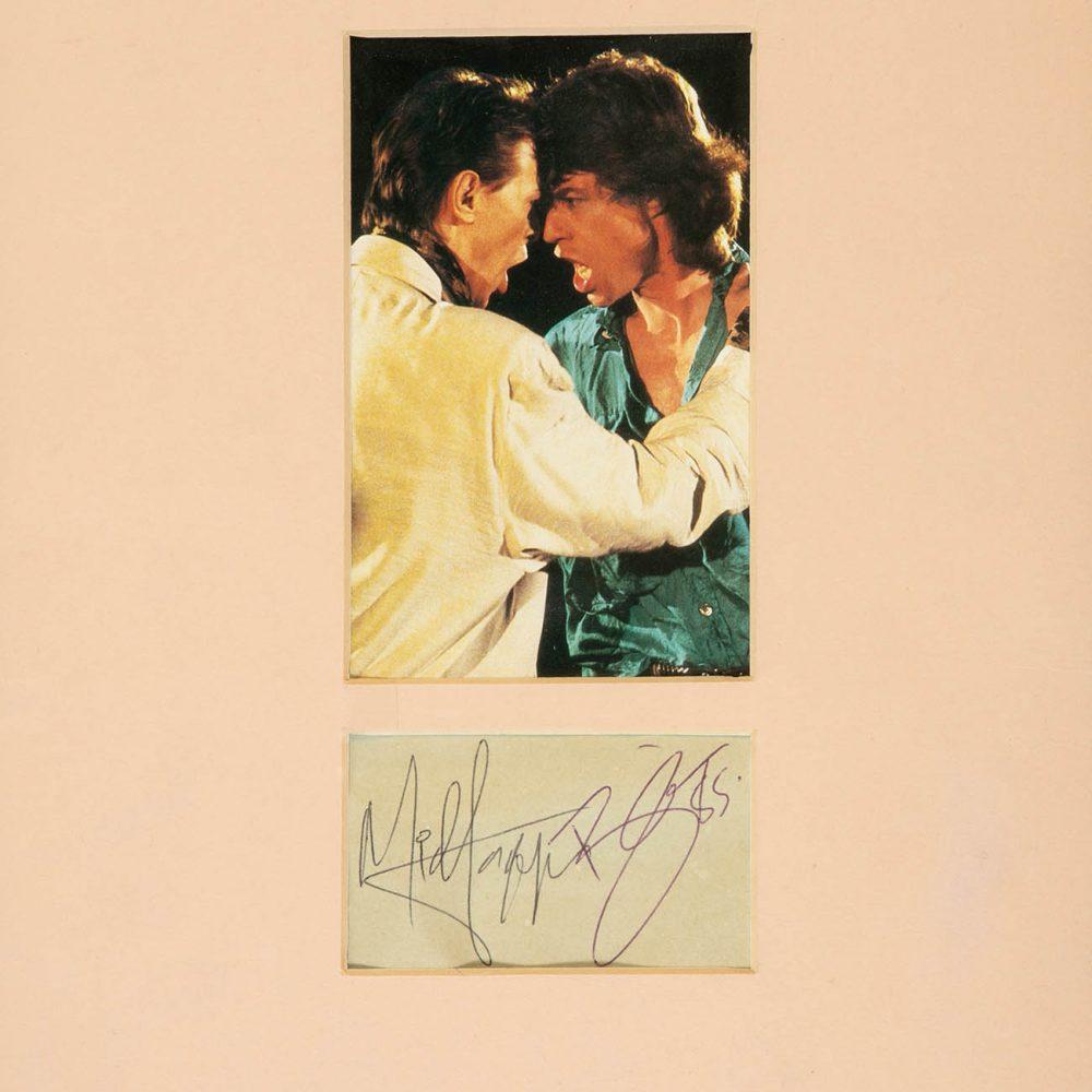 """DAVID BOWIE Y MICK JAGGER.  Fotografía a color del videoclip """"Dancing in the Street"""" y autógrafos de ambos artistas, 1985."""